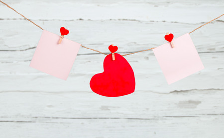 Valentine concept, red heart hang on wooden background photo