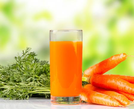 zanahorias: Jugo de zanahoria fresco en la mesa de madera con fondo de naturaleza verde