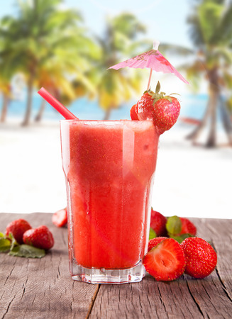 Strawberry cocktail on wooden table with beach background, summer concept, fresh berry fruits