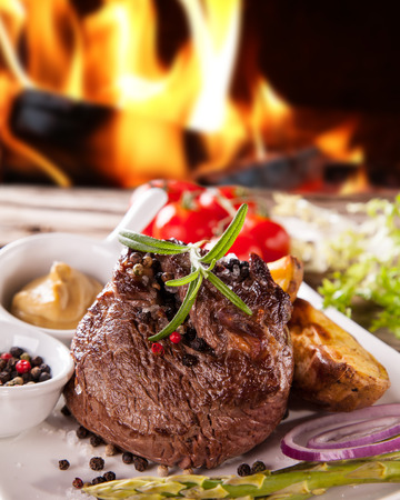 beef meat: Delicious beef steakes on wood with fire background