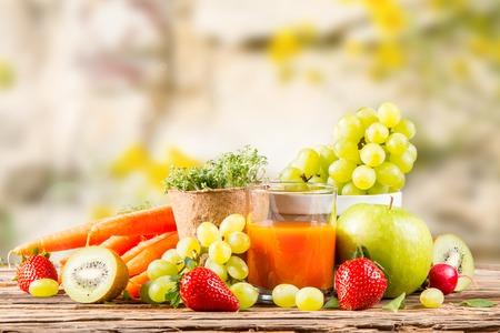 木製のテーブル、水まき缶、種子、植物野菜にんじんジュース、新鮮なフルーツ ガーデンのコンセプト