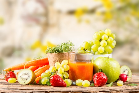 Garden concept, fresh fruits, carrot juice and vegetables on wooden table, watering can, seeds, plants