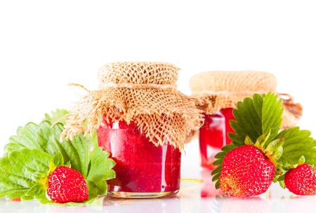 Strawberry jam and fresh berries isolated on white photo