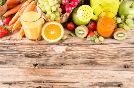 Fresh juice, fruits and vegetables on wooden table