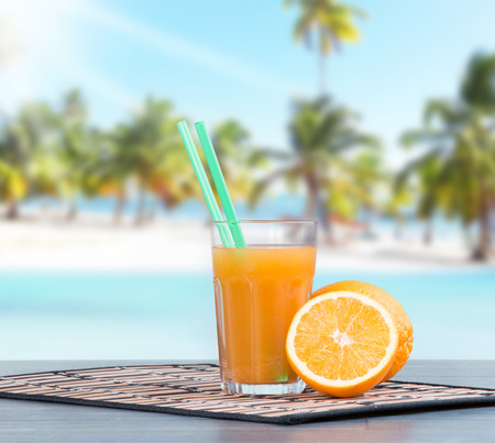 multivitamin: Fresh juice, orange and multivitamin on wooden table with tropical beach background