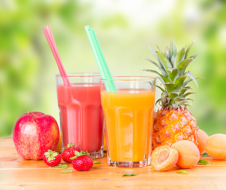 fruits juice: Fresh juice with fruits on wooden table with nature green background