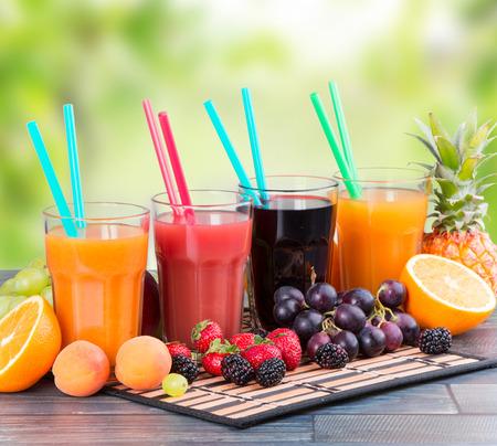 vaso de jugo: El jugo fresco con frutas sobre la mesa de madera con la naturaleza de fondo verde