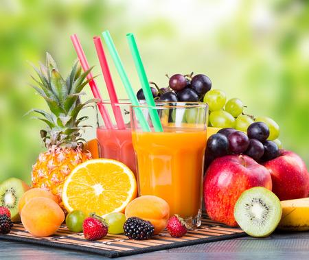 jugo de frutas: El jugo fresco con frutas sobre la mesa de madera con la naturaleza de fondo verde