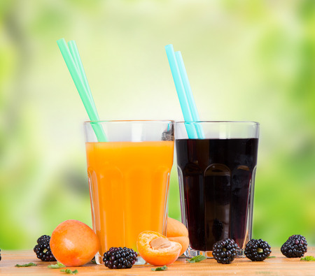 multivitamin: Fresh juice orange, multivitamin on wooden table, fruits and nature green background