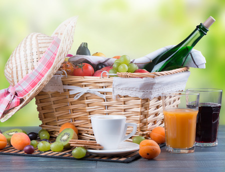 picnic food: picnic on wooden table with a basket of food