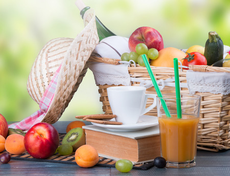 picnic food: Summer picnic on wooden table with a basket of food, nature green background