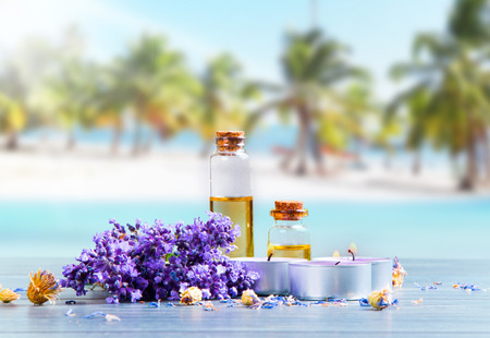 healthcare and beauty: spa massage setting, lavender product, oil on wooden and tropical beach background Stock Photo