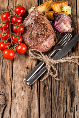 wooden surface: Delicious beef steak on wooden table. Fresh beef meal and grilled vegetable
