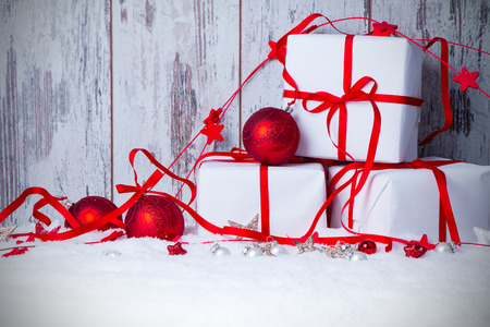 red evening: Christmas background with decorations and gift boxes on wooden board