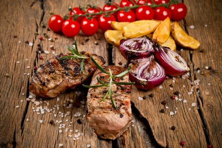 wooden surface: Fresh steaks with flames on background Stock Photo