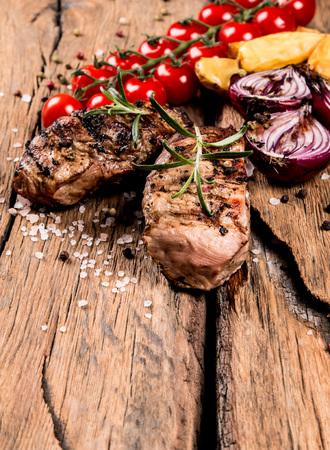 wooden surface: Fresh steak on wooden background