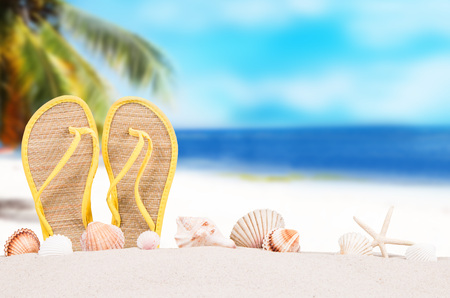 Summer concept of sandy beach, flip flops and starfish. Stock Photo