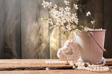 perls: Spring flowers, heart and perls on wooden background Stock Photo