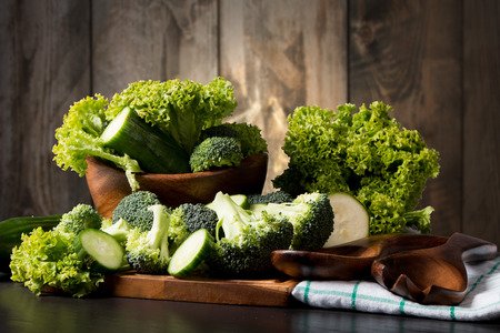 Fresh broccoli on black stone with wooden background