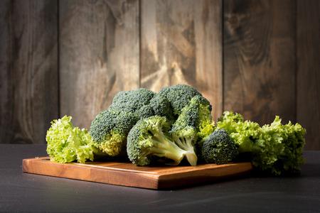 Fresh broccoli on black stone with wooden background Reklamní fotografie