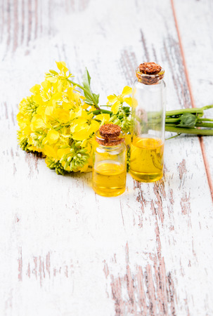 biodiesel: Rape oil and flower on wooden background Stock Photo