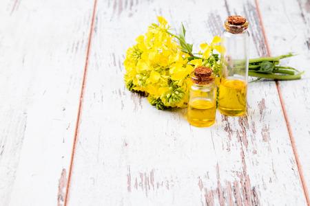 oil rape: Rape oil and flower on wooden background Stock Photo