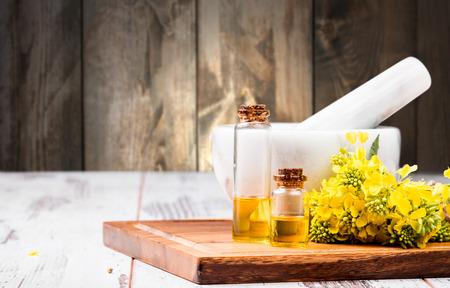 oil rape: Rape oil and flower on wooden table Stock Photo