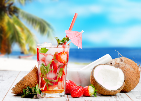 mohito: Mojito strawberry drink on wood with blur beach background