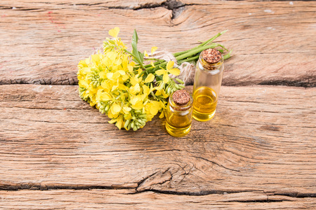 Rape oil and flower on wooden table Stock Photo
