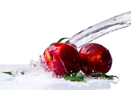 Fresh Nectarine, fruits falling in water splash, isolated on white background