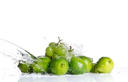 Fresh lime, fruits falling in water splash, isolated on white background Stock Photo