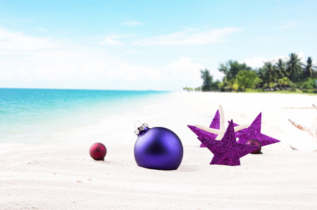 Christmas balls, ornament on beach - concept of warm weather. Christmas celebration concept Stock Photo