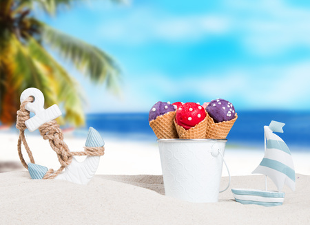 Ice cream in bucket beside summer decorations on sandy beach Banque d'images - 115606590