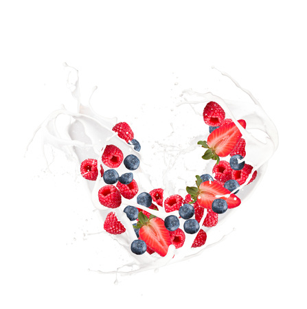 Milk splash with raspberry, blueberry and strawberry isolated on white
