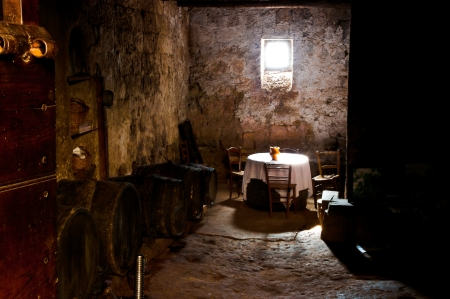 dimly: Old cellar lit basement of a small window with table and chairs for wine pitcher hit by the ray of sunshine piercing the darkness Stock Photo