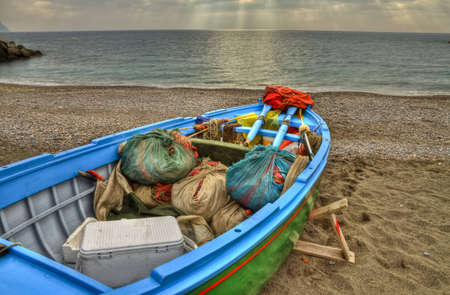skiff: Fishing boat on the beach of Atrani (SA) containing the working tools: nets, paddles, insulated containers and buoys