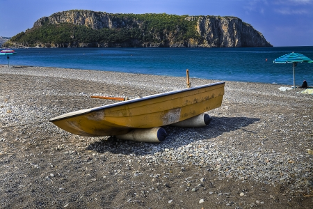 beach and boat. On the horizon is evidence of the island of Dino photo