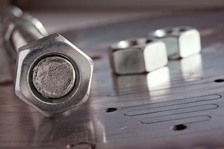 schrauben: Stahl Mutter am Schraube auf Metallplatte mit ein paar N�sse auf Hintergrund