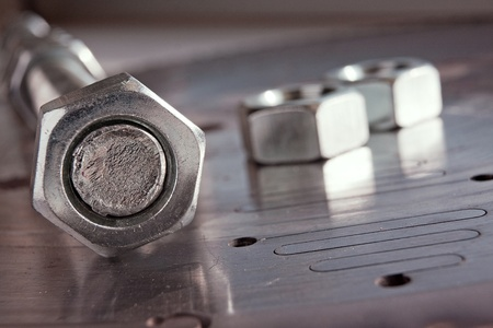 bolts and nuts: Steel nut on screw on metal plate with a few nuts on background Stock Photo