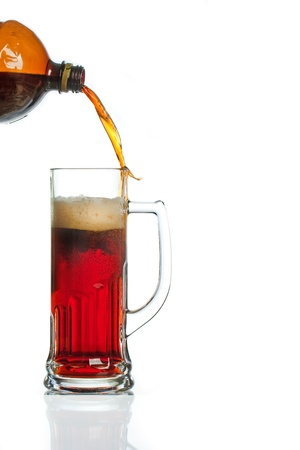 against the flow: Flow of beer from bottle missing glass mug against white background