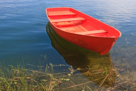 rowing boat: Red rowing boat on lake