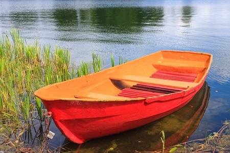 Red rowing boat on lake photo