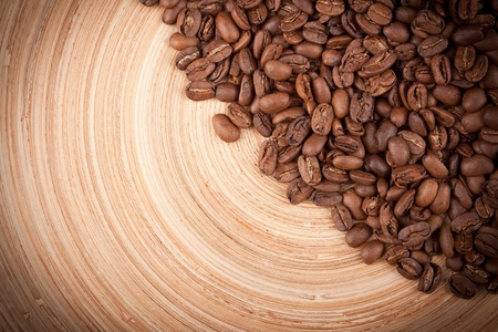 Heap of coffee beans on wooden plate