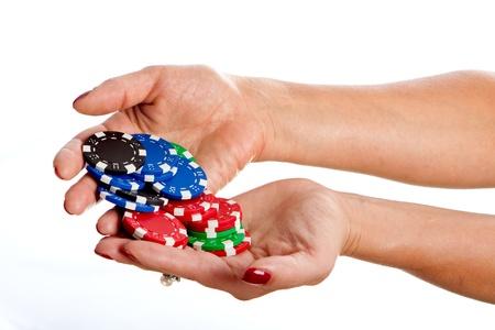 Female hands holding poker chips against white background photo