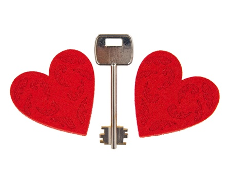 Key between two hearts isolated on white background photo