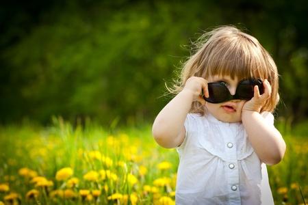 Little girl in a dandelion meadow puting sunglasses upside down Stock Photo