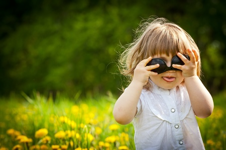 Little girl in a dandelion meadow puting sunglasses upside down and showing the tongue photo