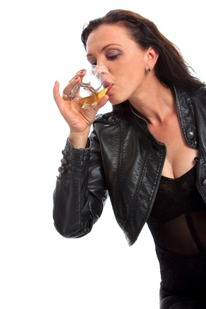 Girl in black drinking glass of whiskey against white background Stock Photo