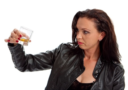 Girl in black jacket looking to glass of  whiskey photo