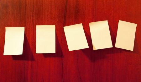Line of five sticky paper reminder notes on brown wall photo